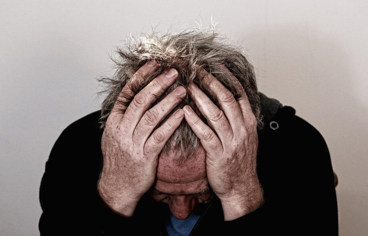 Mann der sich bei Clusterkopfschmerzen die Hände an den Kopf hält