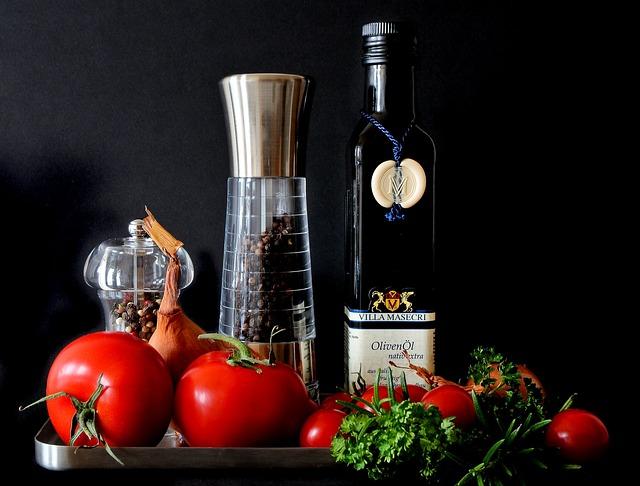 Eine Flasche Olivenöl steht zwischen einigen Mediterranen Lebensmitteln.