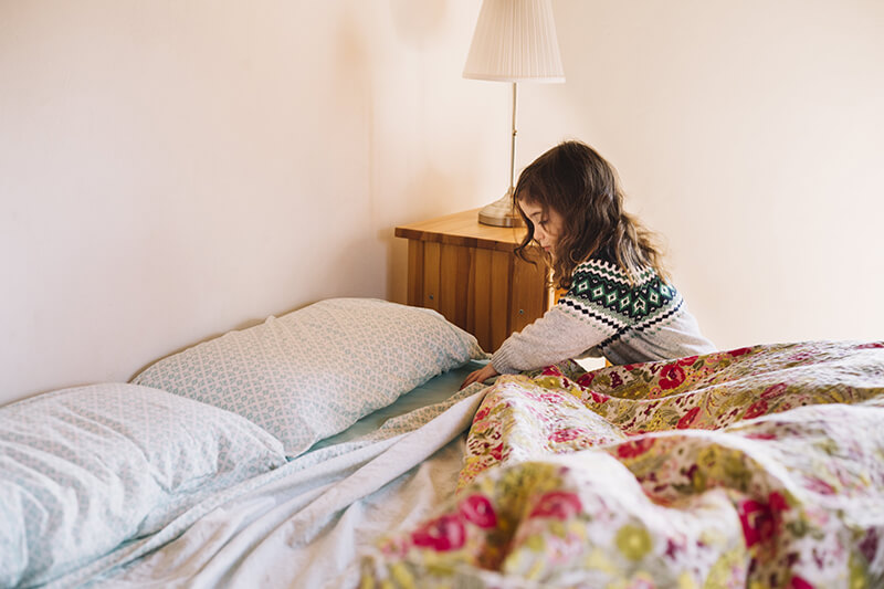 Mädchen macht das Bett