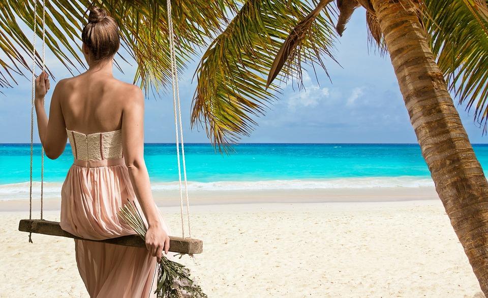 Frau erholt sich in einer Schaukel am Strand