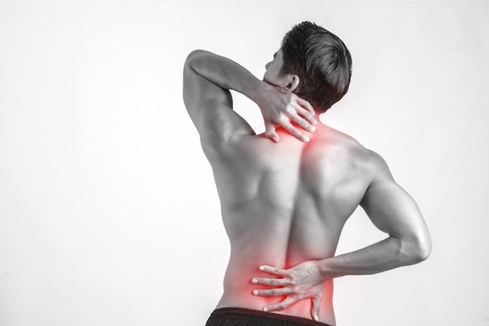 Mann mit Muskelkater am Nacken und unteren Rücken in schwarz-weiß mit grauem Hintergrund