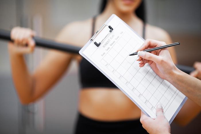 fitnessplan-sporttrainer-belaeuft-sich-auf-trainingsplan-nahaufnahme