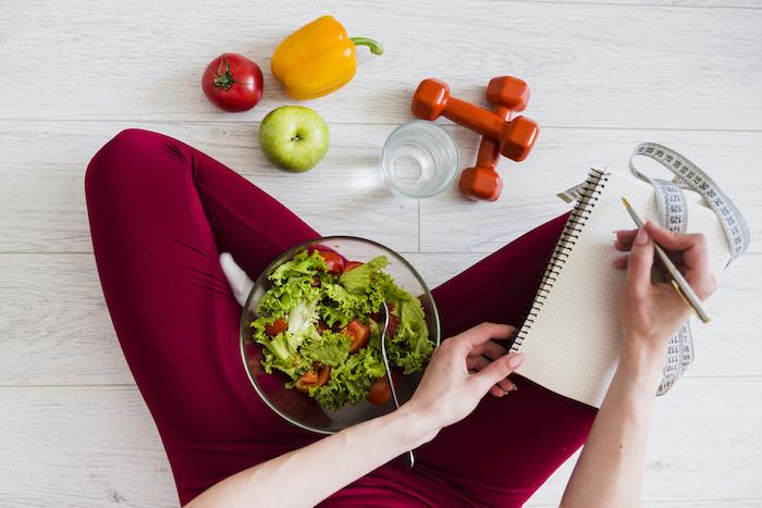 Frau im Schneidersitz mit Salat Obst und Gemüse erstellt Trainingsplan für Fitness