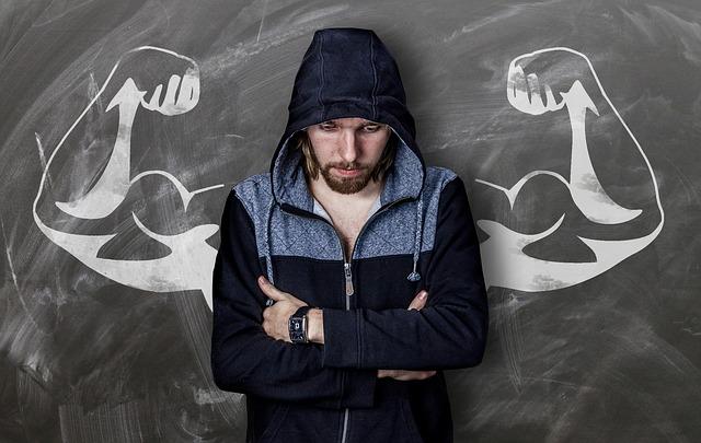 schlanker Mann steht vor einer Tafel mit Muskulösen Armen