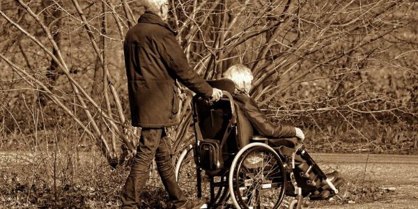 Mann schiebt Frau mit Demenz im Rollstuhl