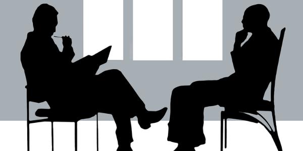 Zwei Personen führen eine verbale Überprüfung der Vaskulären Demenz durch