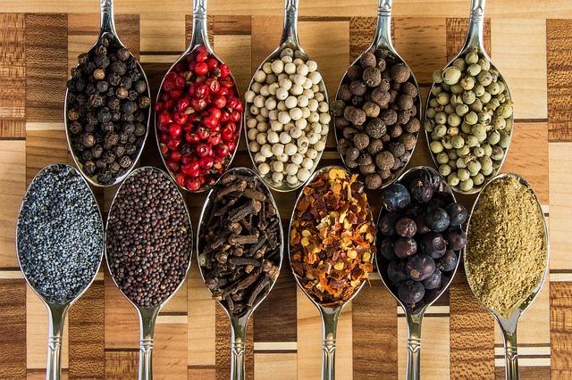 Elf verschiedene Gewürze die den Appetit anregen sollen liegen in Elf Löffeln verteilt.