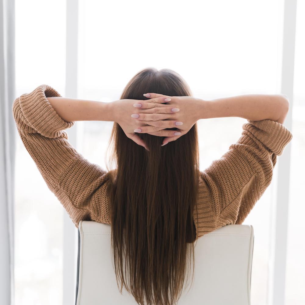 frau-die-auf-einem-stuhl-von-hinten-ansicht-entspannt