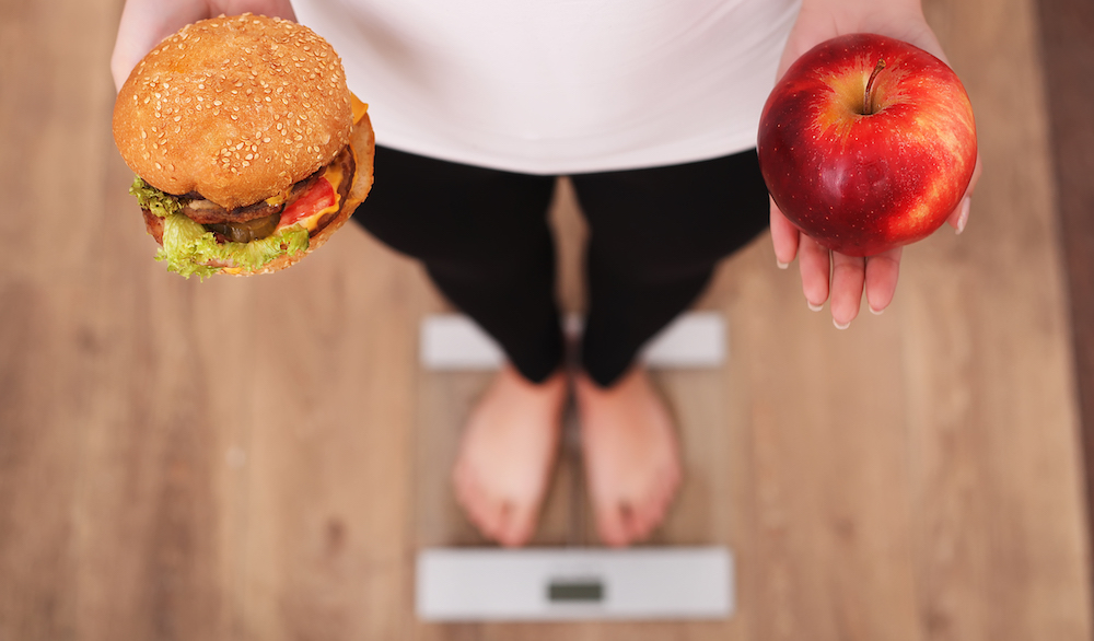 frau steht auf waage hält hamburger und apfel in der hand bekämpft skinny fat