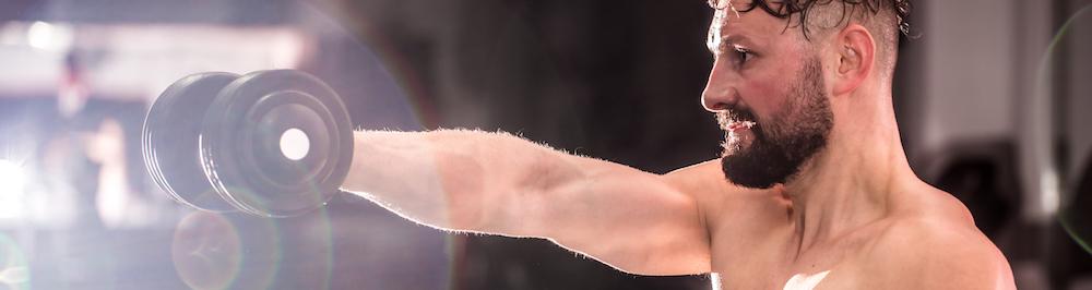 Athletischer Mann hebt eine kurzhantel als Schulterübung für schnellen Muskelaufbau