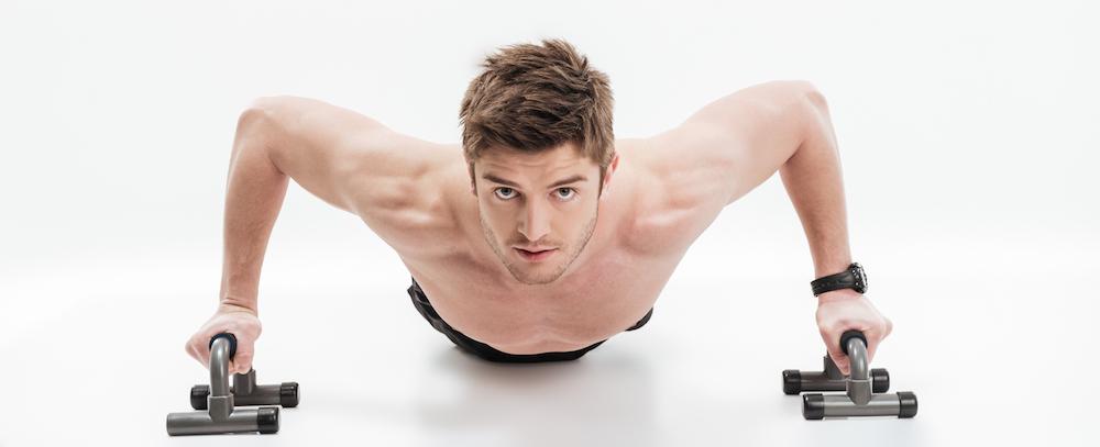 junger mann macht push-ups mit Liegestützgriffen