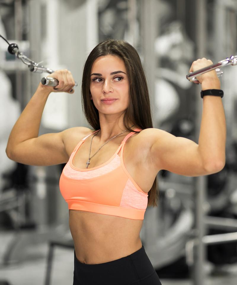 frau im Fitnessstudio trainiert ihren Bizeps und macht bodybuilding