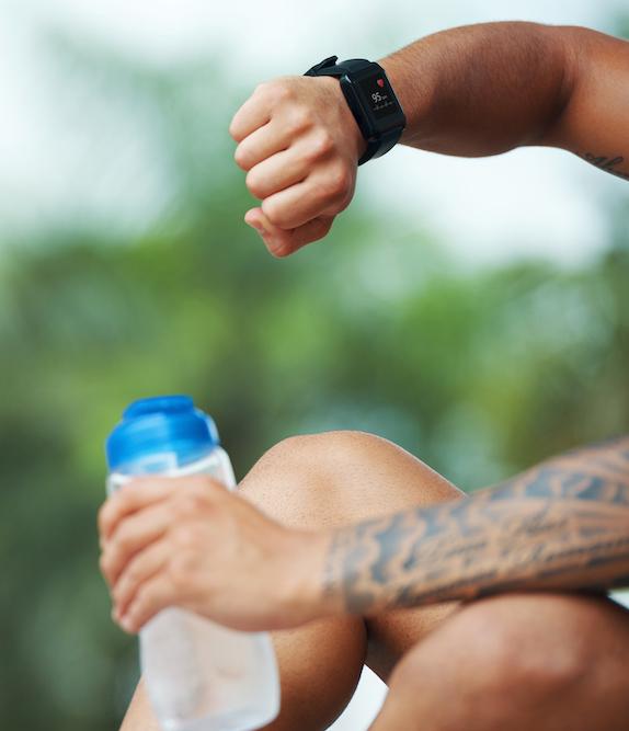 sportler-mit-wasserflasche-der-draussen-smartwatch-ueberprueft
