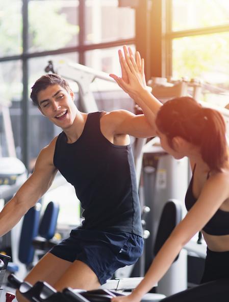gesunde-frau-und-mann-mit-der-laufenden-sportkleidung-die-hohe-fuenf-beim-trainieren-auf-uebung-an-der-turnhalle-sich-gibt