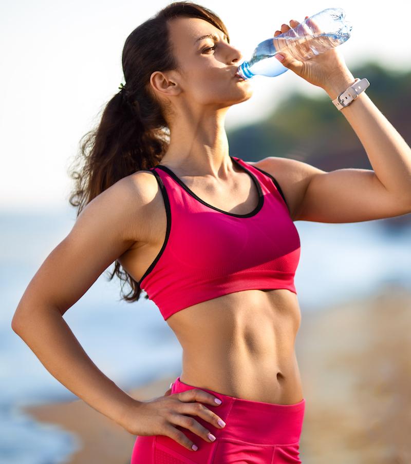 Frau macht eine Pause nach dem Sport und trinkt Wasser bei warem Wetter am Strand
