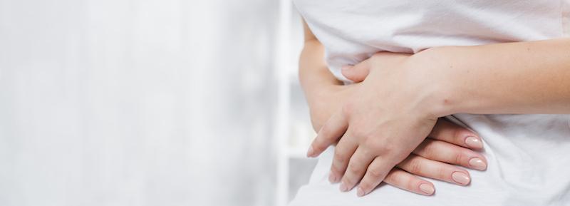 Mittig geschnittenes Bild mit Frau die Magenschmerzen hat und sich den Bauch hält leidet unter Durchfall und Schwindel