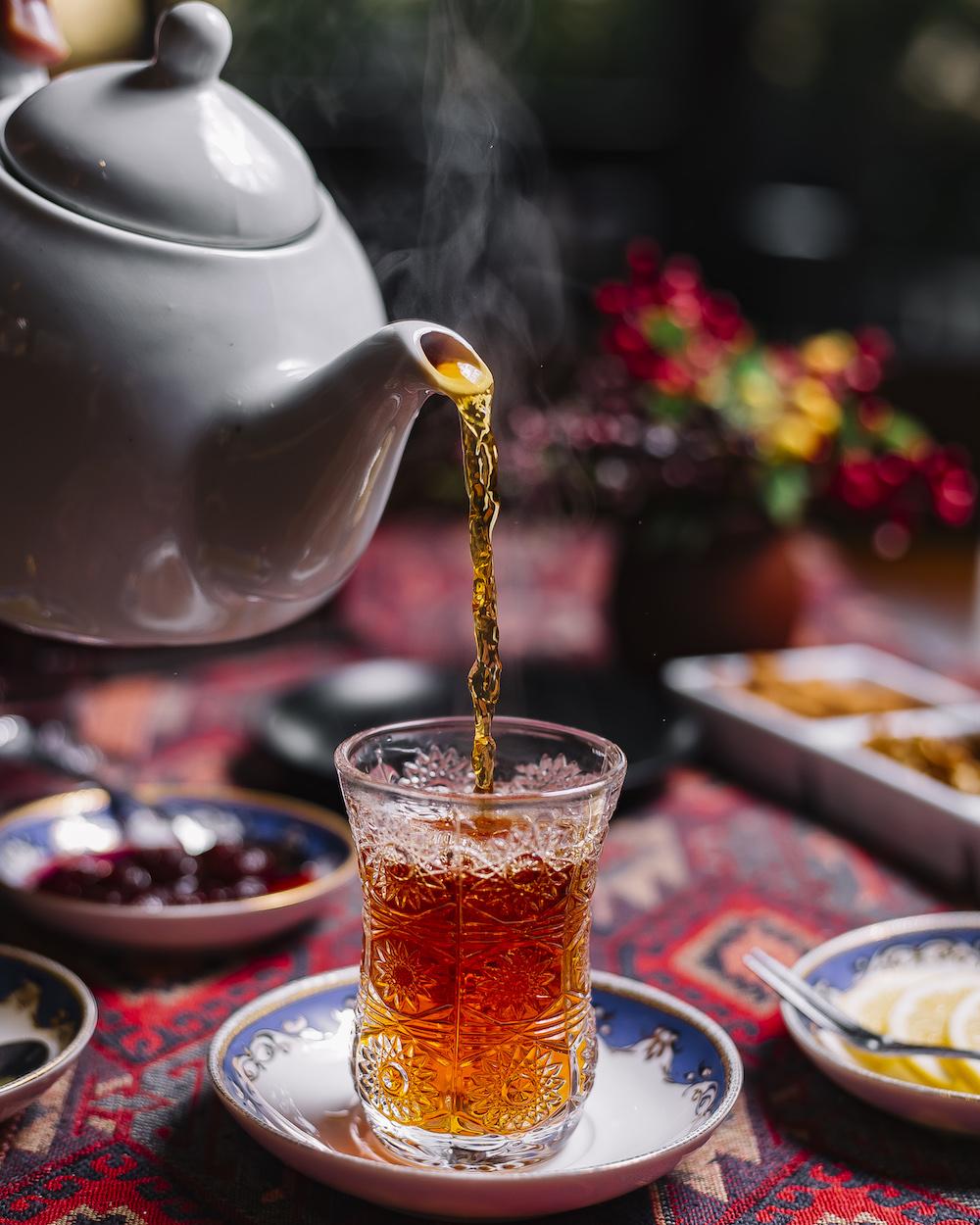 seitenansicht auf schwarzer Tee von weißer Teekanne gießen in ein kleines Glass