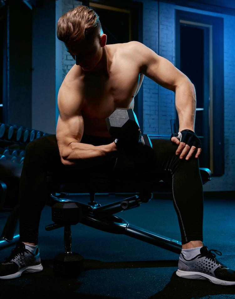 Junger mann trainiert seinen Bizeps mit Kurzhantel auf einer Bank und unterstützt schnellen Muskelaufbau