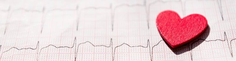 ausschnitt-von-einem-elektrokardiogramm-in-der-papierform-mit-rotes-hoelzernes-herz-ecg-oder-ekg-papierhintergrundbeschaffenheit-medizin-und-gesundheitskonzept