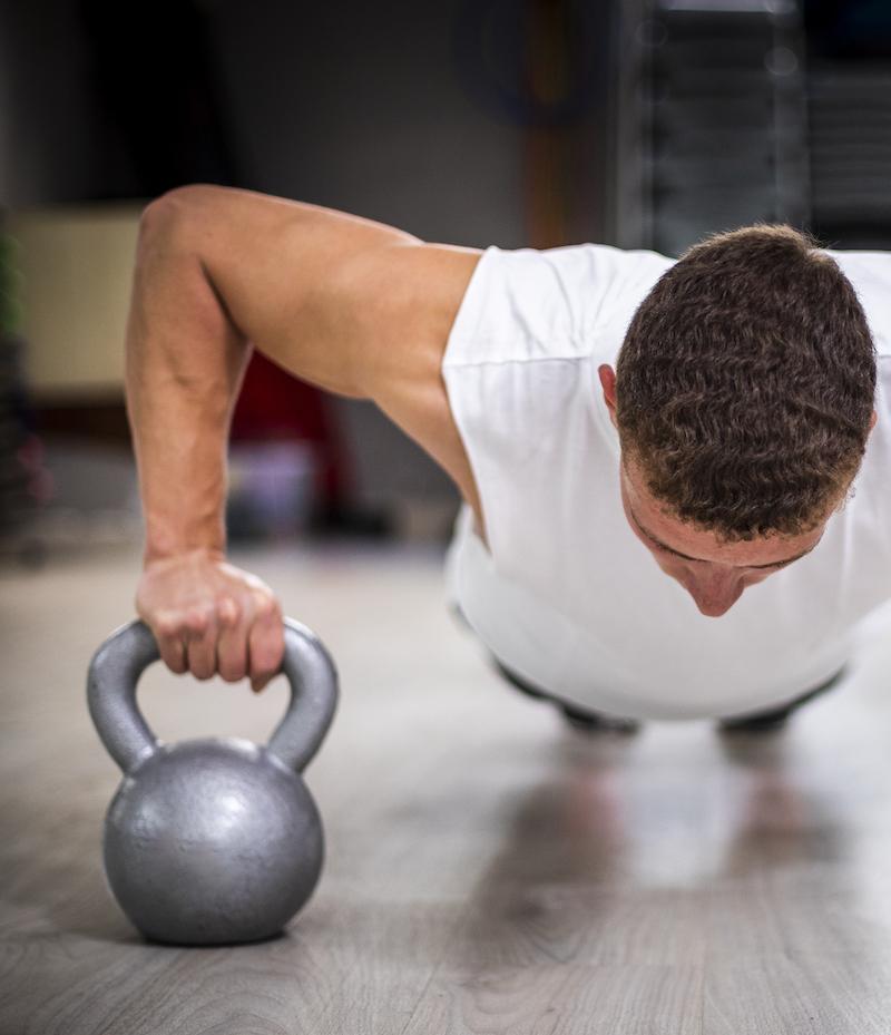 frontal ansicht athletischer mann macht Liegestütze auf kettlebell