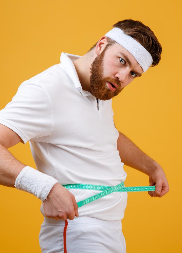 Skinny fat mann vor gelbem hintergrund in sport klamotten misst deinen bauchumfang mit maßband