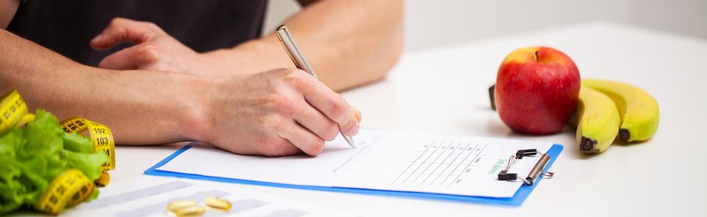 mann schreibt einen ernährungsplan auf notitzbrett auf weißem tisch mit obst und Gemüse