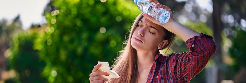 schwitzende-frau-leidet-unter-kreislaufproblemen-und-schwindel-die-auf-einer-bank-ruht-und-mit-einer-flasche-kaltem-erfrischendem-wasser-in-einem-park-in-heissem-sommerwetter-abkuehlt