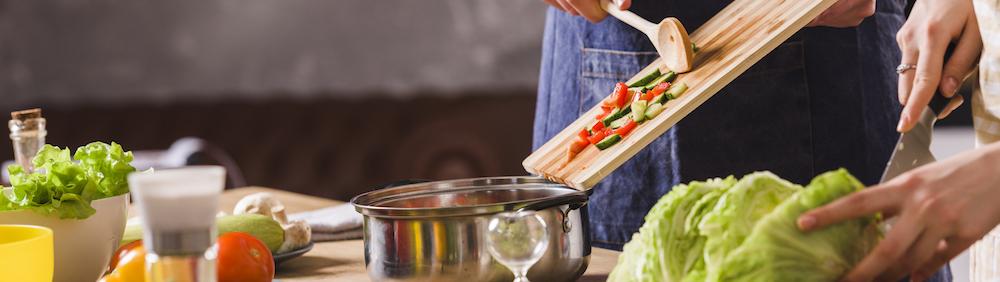 Pärchen kochen gesundes Essen zur Unterstützung des Muskelaufbaus
