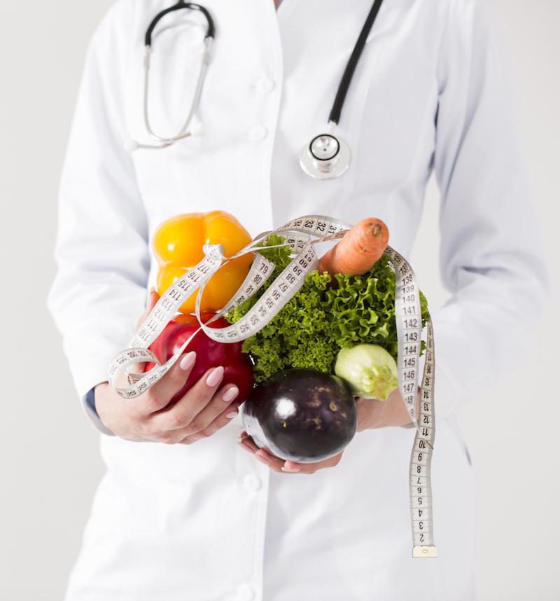 ärztin hält gemüse mit Maßband als gesunden ernährungsplan
