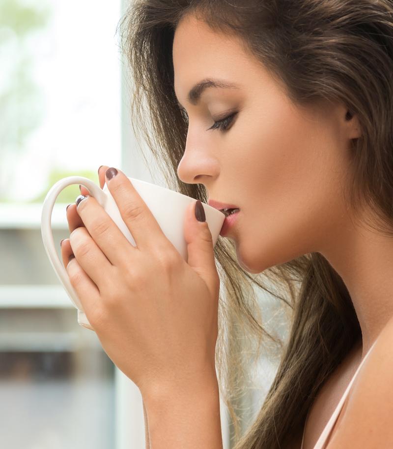 junge Frau Kreislaufproblemen durch Flüssigkeitsmangel trinkt Kräutertee