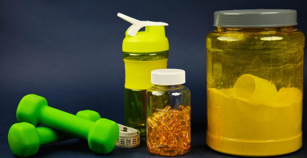 BCAA und protein in behältern mit kurzhanteln shaker und maßband