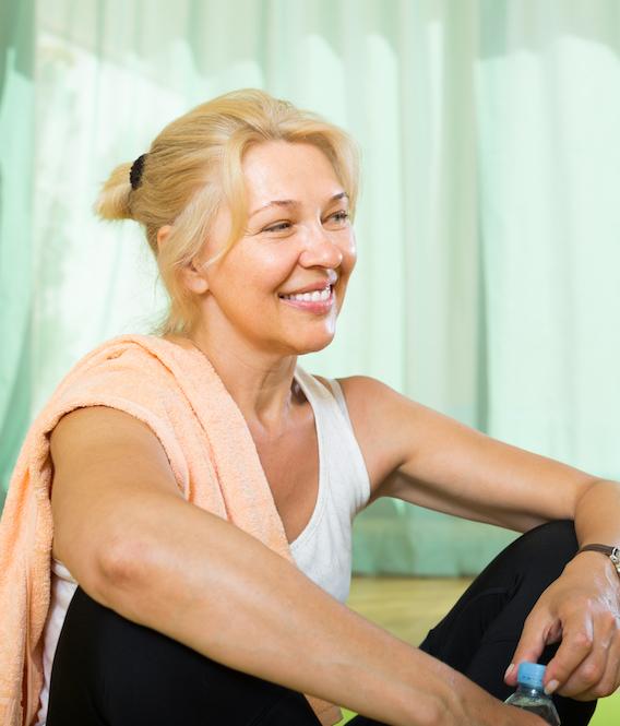 alter Frau lächelt nach dem Sport und trinkt Wasser