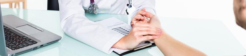 Ärztin untersucht den Blutdruck des Patienten durch Puls messen