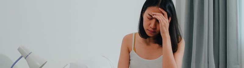 junge Frau leidet an einem Schwächeanfall sitzt im Bett und hält sich mit der linken Hand die Stirn