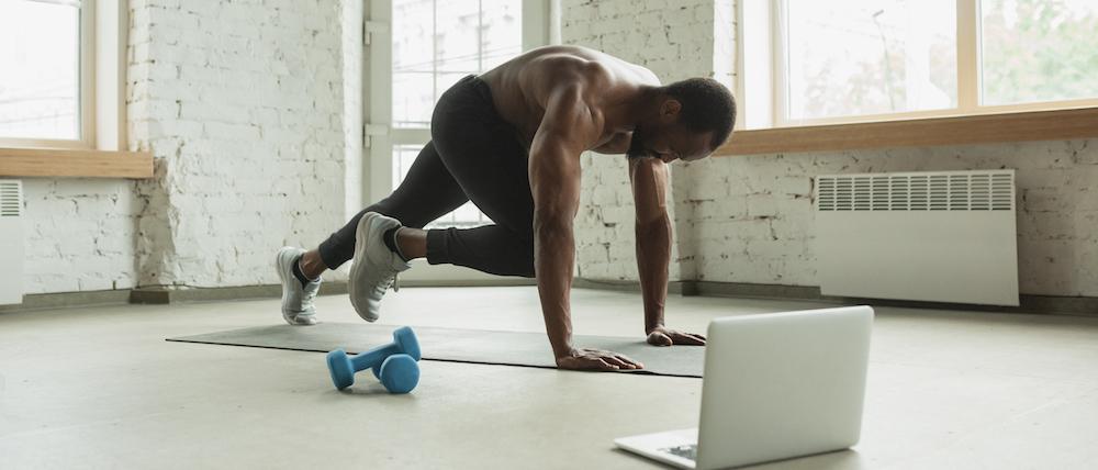 mann trainiert zuhause mit laptop online fitness