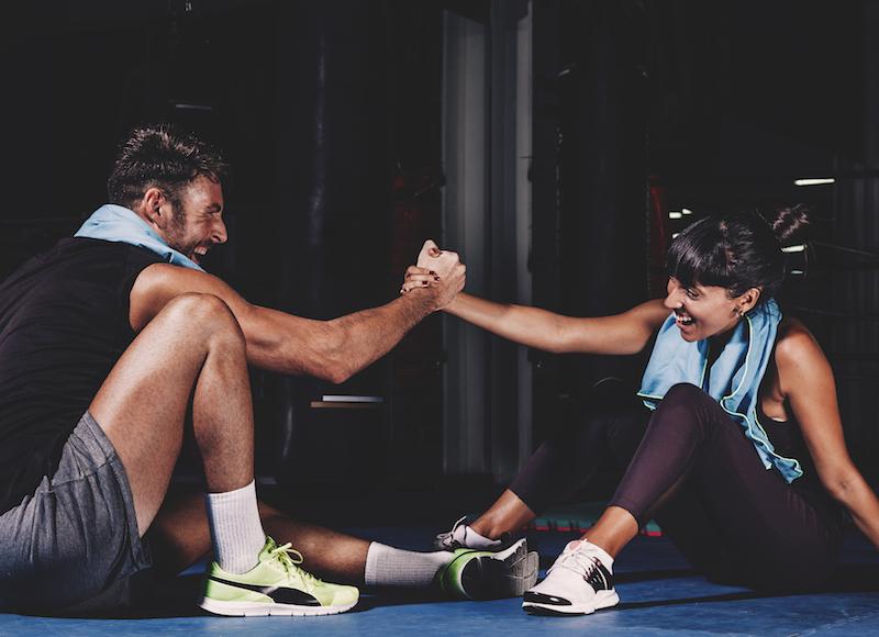 Muskelaufbau mann und frau machen eine pause nach dem workout hände einschlagen