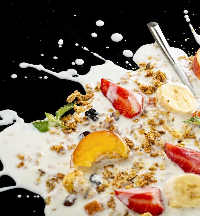 protein joghurt splash mit früchten und granola vor schwarzem Hintergrund