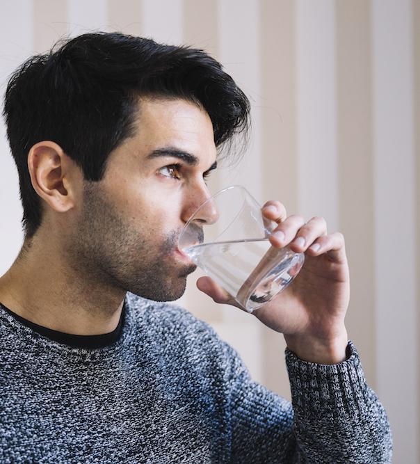 mann trinkt ein glas Wasser um zu hydrieren