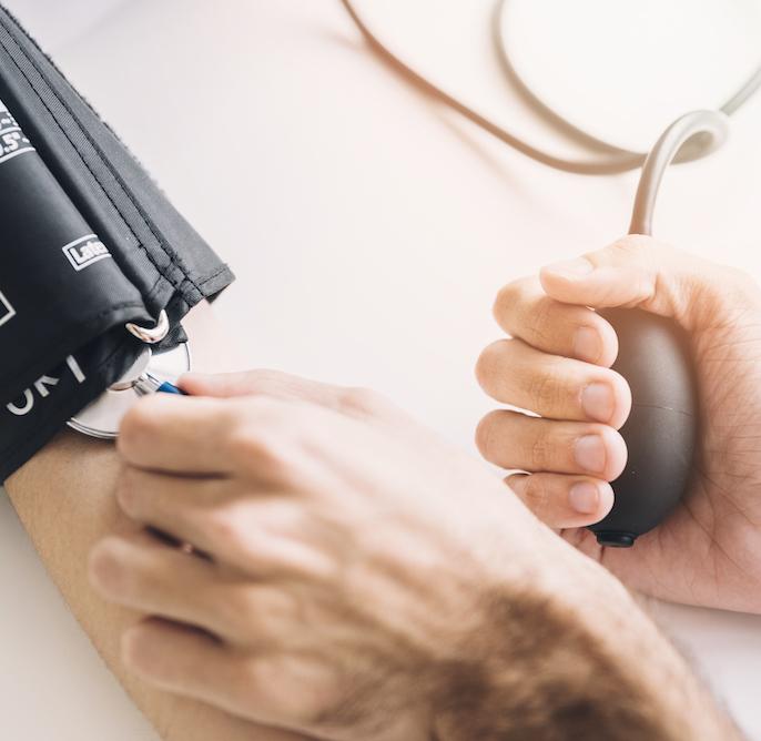 nahaufnahme-der-hand-eines-doktors-die-blutdruck-des-patienten-ueberprueft