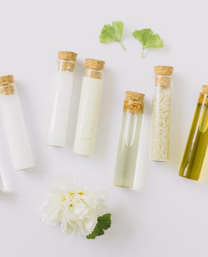 verschiedene-kosmetische-produkte-im-reagenzglas-mit-gingko-blatt-und-blume-auf-weissem-hintergrund