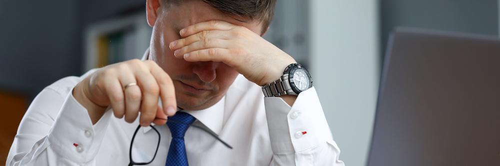mueder-maennlicher-bueroangestellter-der-am-tisch-sitzt-der-sich-ausruht-leidet-unter-Schwaecheanfall-und-kreislaufproblemen