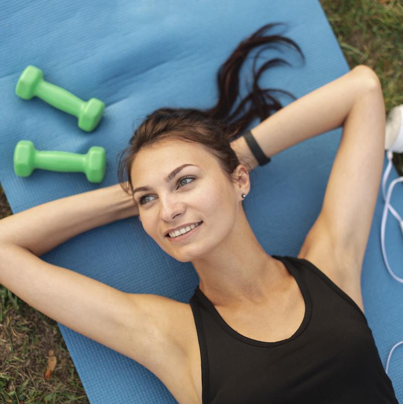 fitness frau liegt auf dem Rücken und macht eine Pause nach dem fitness training