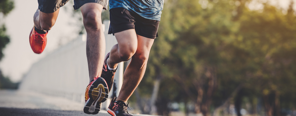 zwei junge maenner beim joggen machen Ausdauertraining und herzkreislauftraining durch laufen auf asphaltierter Strasse