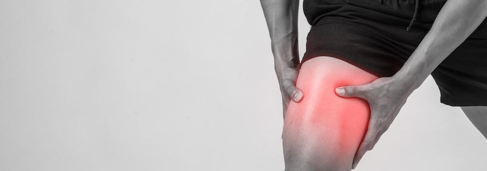 mann hält sich den oberschenkel wegen muskelkater schwarz weiß mit roter veranschaulichung