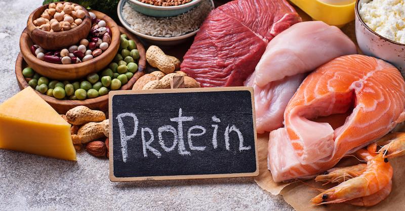 Tisch mit eiweißhaltigen Lebensmitteln und auf Tafel Protein geschrieben