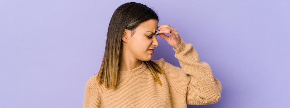junge-frau-auf-lila-wand-die-einen-kopfschmerz-hat-und-ihre-stirn-beruehrt-leidet-unter-kreislaufproblemen-mit-drohender-ohnmacht
