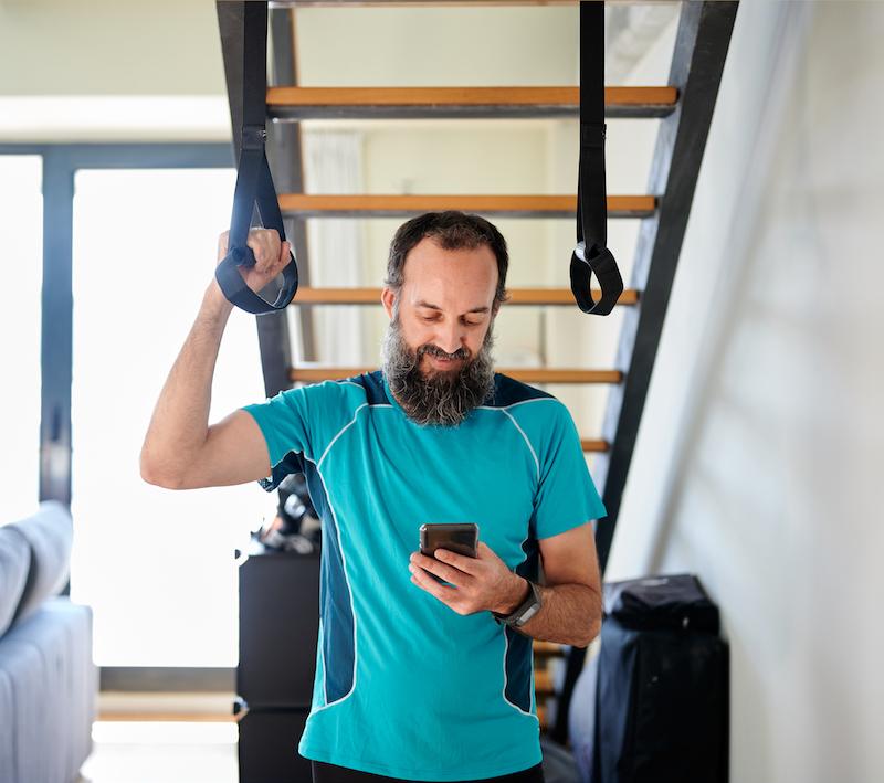 mann macht eine Pause von Rückentraining zuhause schaut auf sein Handy