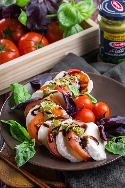 Ein Tomaten Mozzarella Salat ist in einer braunen Schale zubereitet worden