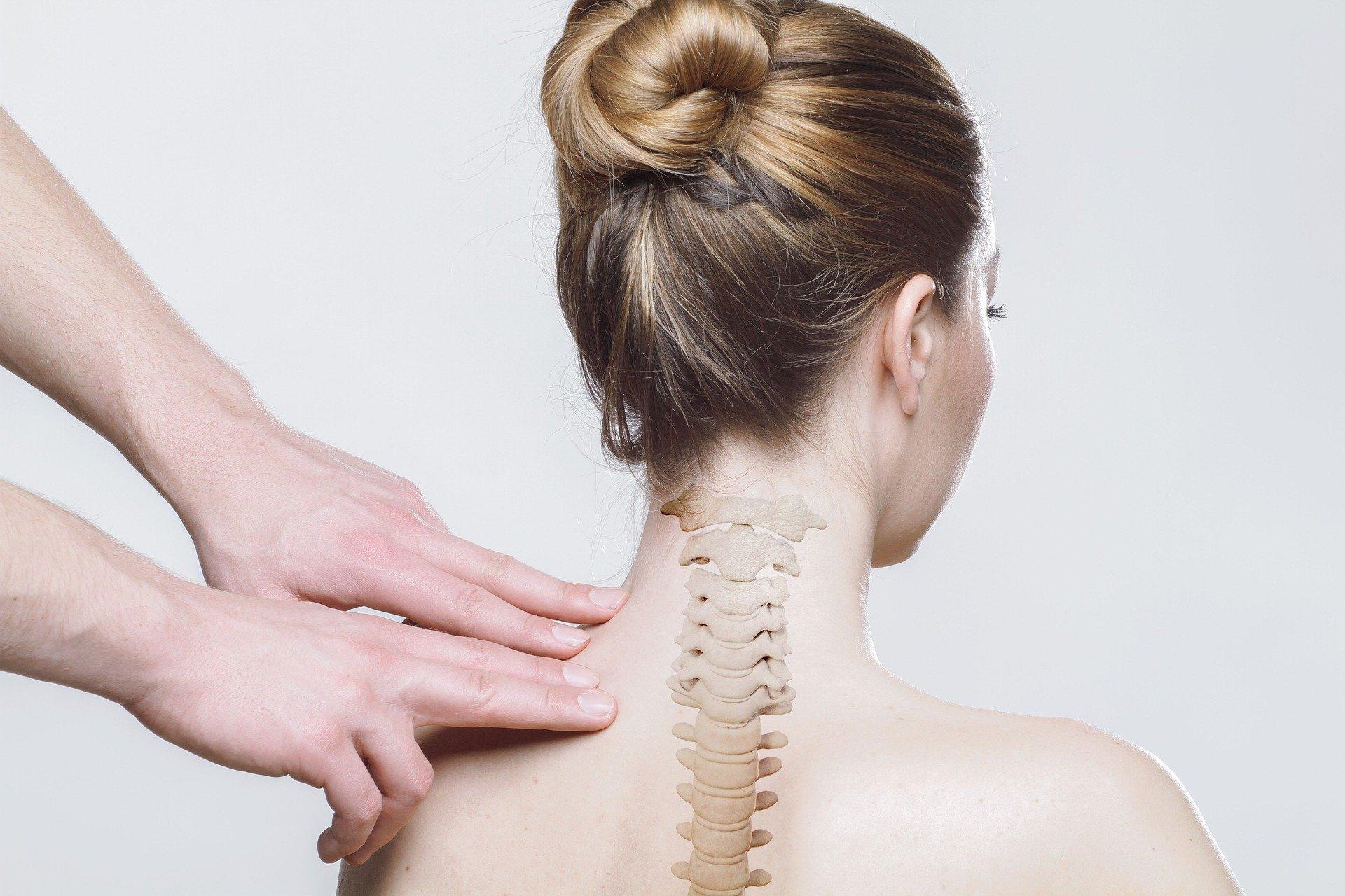 Arzt untersucht die Halswirbelsäule einer Patientin