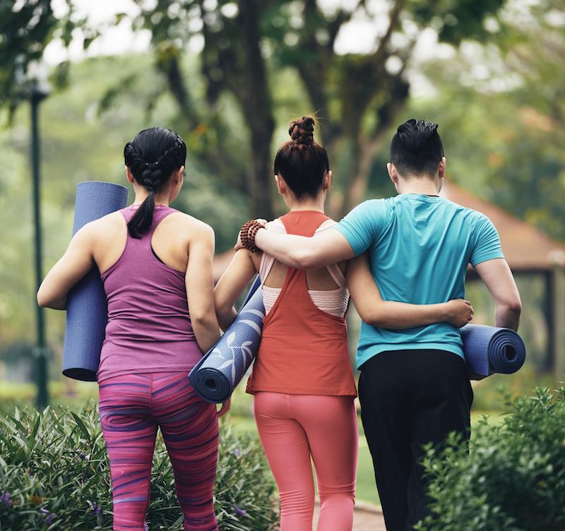 junge leute gehen zur rückenschule mit yoga matte
